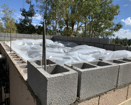 New cinder blocks going in to raise the roof. Plastic to protect the equipment.